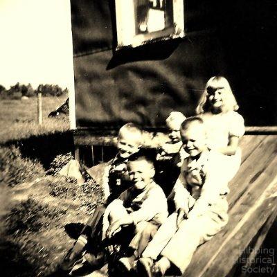 Conklin children on door to root cellar, 1951